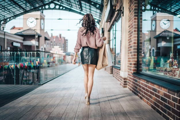 Atrakcyjna długonoga brunetka kobieta ubrana w skórzaną krótką spódniczkę i buty na obcasie idąc przez duże centrum handlowe, trzymając w ręku kilka papierowych toreb