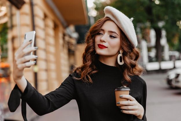 Atrakcyjna długowłosa dziewczyna używa telefonu do selfie na ulicy. niesamowita imbirowa kobieta korzystająca z kawy na świeżym powietrzu.