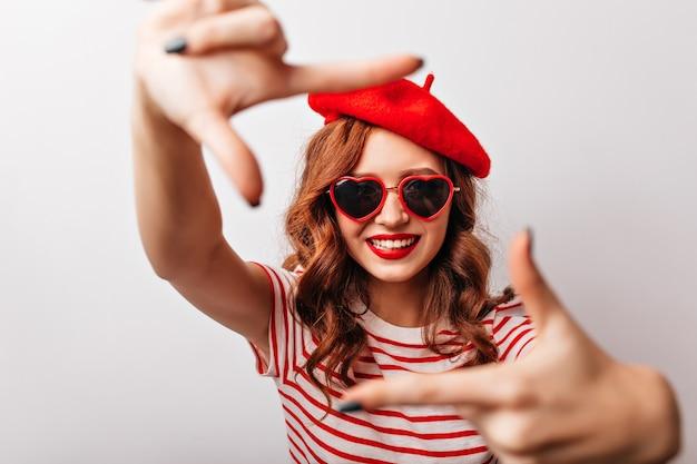 Atrakcyjna długowłosa dziewczyna w stylowych okularach przeciwsłonecznych, uśmiechając się na białej ścianie. fascynująca pani pozująca we francuskim berecie.
