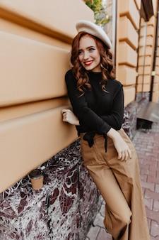 Atrakcyjna długowłosa kobieta w brązowych spodniach stojąc na ulicy. plenerowe zdjęcie wesołej francuskiej dziewczyny.