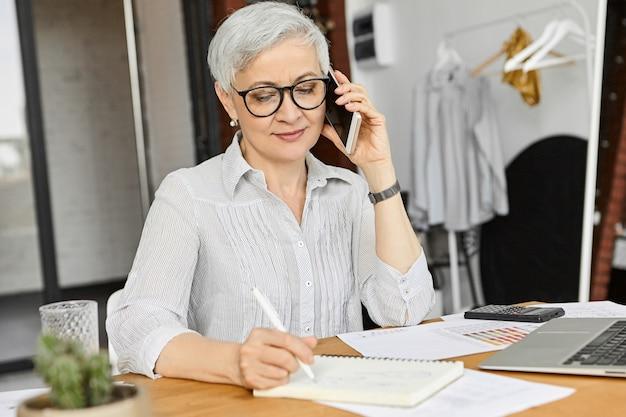 Atrakcyjna dojrzała europejka ceo w bluzce i okularach, prowadząca jednocześnie rozmowę telefoniczną i robienie notatek, zapisująca ważne informacje. nowoczesne gadżety elektroniczne i komunikacja