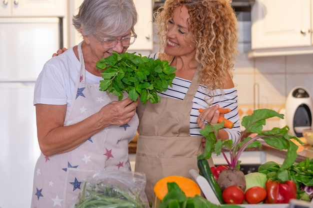 Atrakcyjna dojrzała kobieta z kręconymi włosami w domowej kuchni z matką, która wącha pęczek mięty. na stole mieszanka świeżo zebranych warzyw