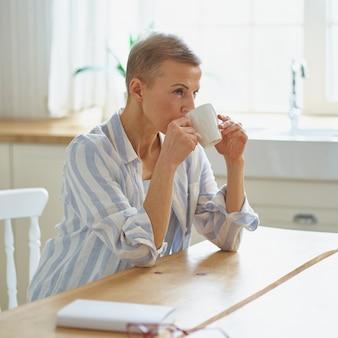 Atrakcyjna dojrzała kobieta zaczyna dzień z kawą siedząc przy drewnianym stole w kuchni