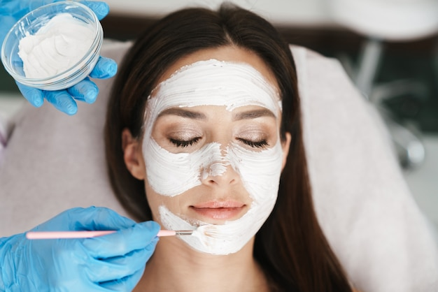 Atrakcyjna dorosła kobieta poddawana zabiegowi kosmetycznemu przez specjalistę podczas leżenia w salonie kosmetycznym