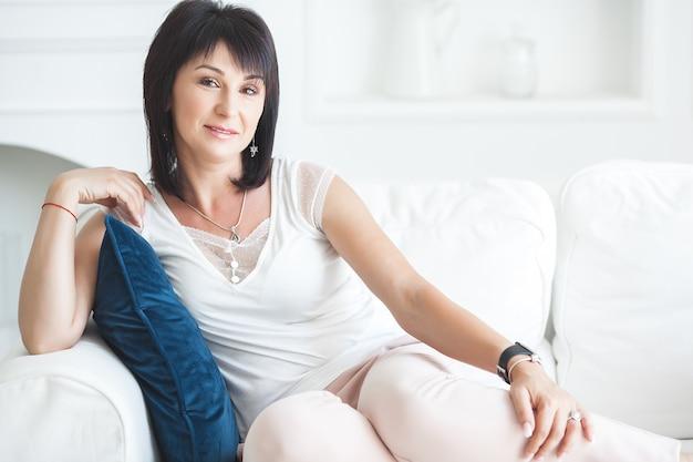 Atrakcyjna dorosła kobieta siedzi na kanapie w pomieszczeniu. piękna kobieta w średnim wieku w domu. portret kobiety 35-40 lat.
