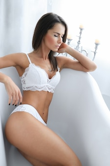 Atrakcyjna dorosła kobieta w białej bieliźnie erotycznej w wannie