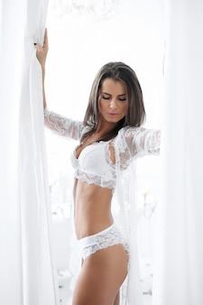 Atrakcyjna dorosła kobieta w białej bieliźnie erotycznej