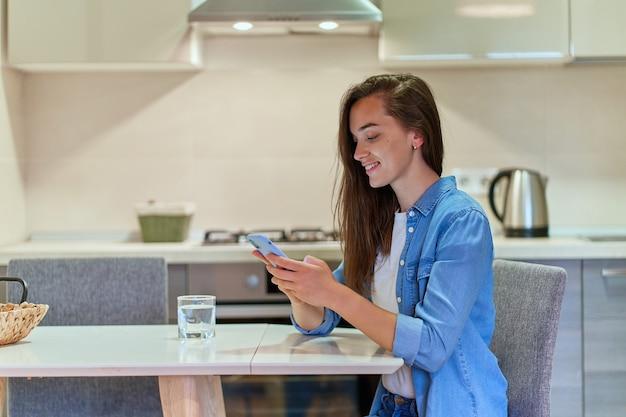 Atrakcyjna dorywczo szczęśliwa nowoczesna młoda dziewczyna za pomocą smartfona do przeglądania i czatowania online