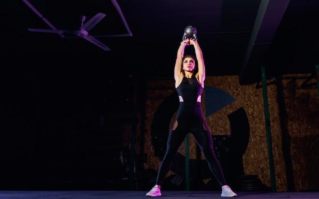 Atrakcyjna dysponowana kobiety atleta wykonuje huśtawki dzwonu czajnika w gym