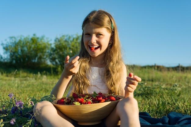 Atrakcyjna dziecko dziewczynka jedzenie truskawek