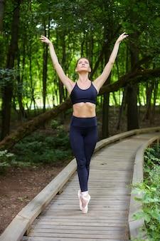 Atrakcyjna dziewczyna baleriny w pointe buty wykonuje ćwiczenia na drewnianej ścieżce w leśnym parku. koncepcja bezpiecznego treningu na świeżym powietrzu
