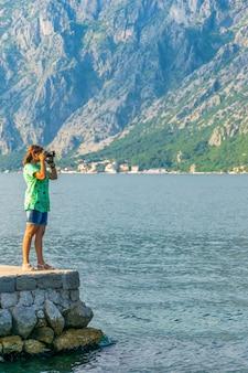 Atrakcyjna dziewczyna fotografuje pejzaż morski.