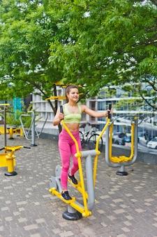 Atrakcyjna dziewczyna lekkoatletycznego robi ćwiczenia na maszynach do ćwiczeń na boisku sportowym na świeżym powietrzu