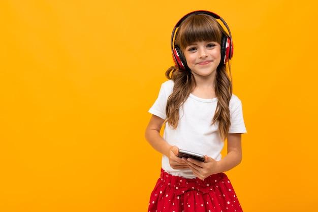 Atrakcyjna dziewczyna lubi słuchać muzyki na słuchawkach i trzymając telefon w dłoniach na pomarańczowym tle studio.