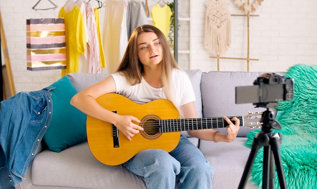 Atrakcyjna dziewczyna nastolatka vlogowania podczas gry na gitarze. atrakcyjna młoda dziewczyna rozmawia i gra na gitarze podczas fotografowania jej wideoblog. młoda ładna vlogerka opowiadająca o muzyce.