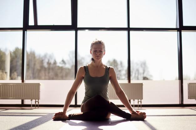 Atrakcyjna dziewczyna o blond włosach siedzi ze skrzyżowanymi nogami i ćwiczy jogę na macie. dziewczyna ćwiczy jogę w nowoczesnym studio z panoramicznym oknem w tle