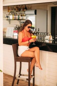 Atrakcyjna dziewczyna odpoczywa w barze na plaży, pić orzeźwiający koktajl. jasne kostiumy kąpielowe i okulary przeciwsłoneczne.
