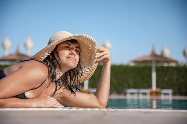 Atrakcyjna dziewczyna odpoczywa w słońcu na sobie słomkowy kapelusz i strój kąpielowy. pojęcie wypoczynku i rekreacji w ciepłym kraju.