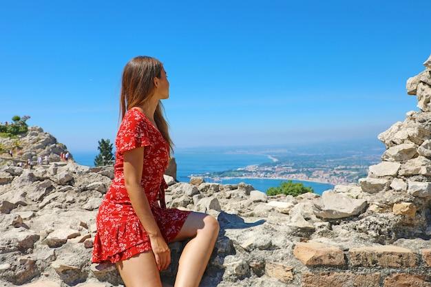 Atrakcyjna dziewczyna patrząc na wioskę taormina z ruin starożytnego greckiego teatru na sycylii, we włoszech