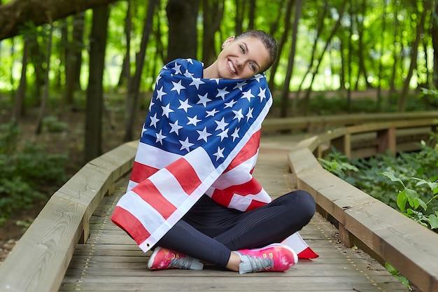 Atrakcyjna dziewczyna pozuje z amerykańską flagą w parku leśnym
