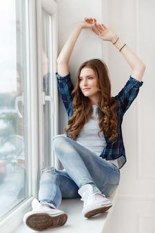 Atrakcyjna dziewczyna przy oknie
