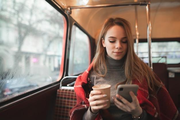 Atrakcyjna dziewczyna przykryta kocem siedzi w przytulnej kawiarni z filiżanką kawy w dłoniach i patrzy na ekran smartfona