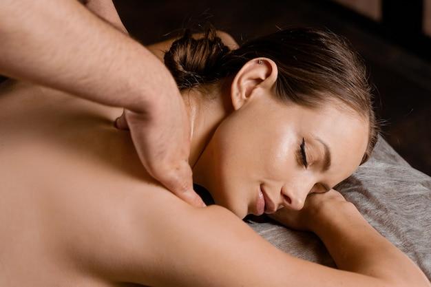 Atrakcyjna dziewczyna relaksuje się na klasyczny masaż procedury w spa. terapia manualna. masażysta robi masaż ramion.