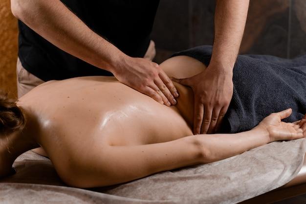 Atrakcyjna dziewczyna relaksuje się na klasyczny masaż procedury w spa. terapia manualna. masażysta wykonuje masaż pleców.