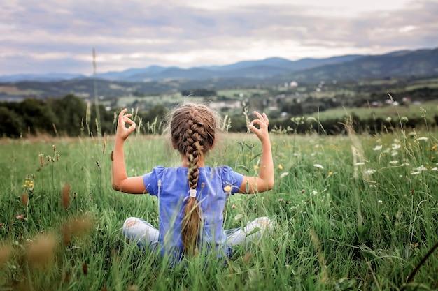 Atrakcyjna dziewczyna robi poranne ćwiczenia na szczycie góry w letniej przyrodzie
