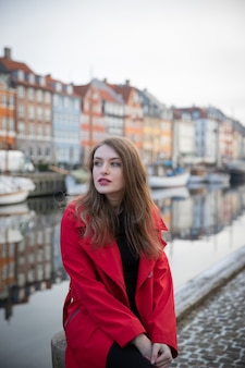Atrakcyjna dziewczyna siedzi, jest turystką i odwiedza nyhavn w kopenhadze w danii. ma na sobie czerwony płaszcz.