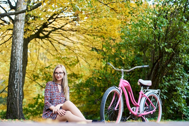 Atrakcyjna dziewczyna siedzi samotnie na ziemi przy różowym dama bicyklu pod wysokim drzewem z złotymi liśćmi