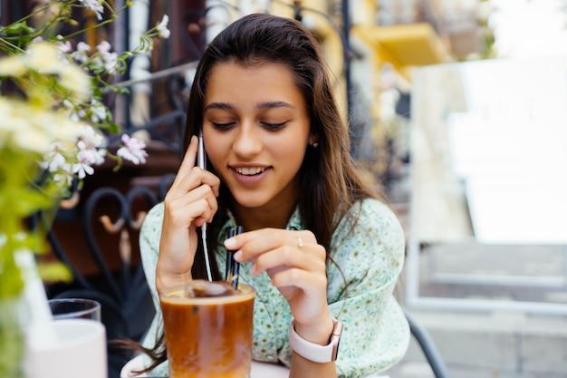 Atrakcyjna dziewczyna siedzi ulicznej kawiarni na świeżym powietrzu, mówi smartfon