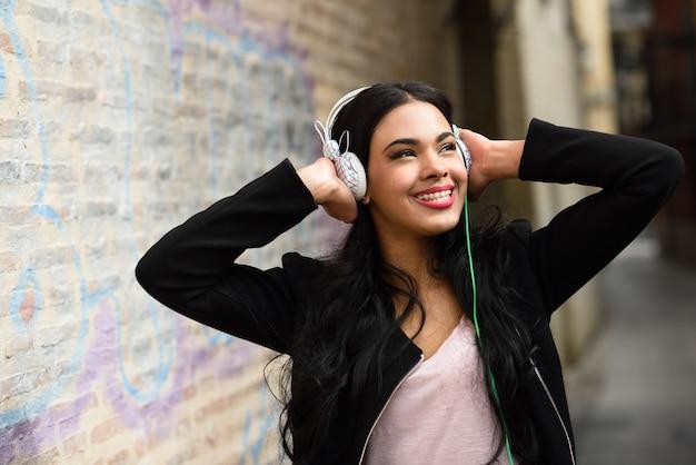 Atrakcyjna dziewczyna słuchania muzyki w słuchawkach