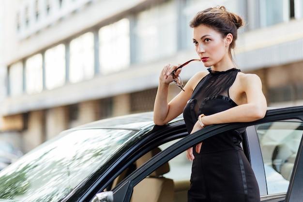 Atrakcyjna dziewczyna stoi blisko samochodu