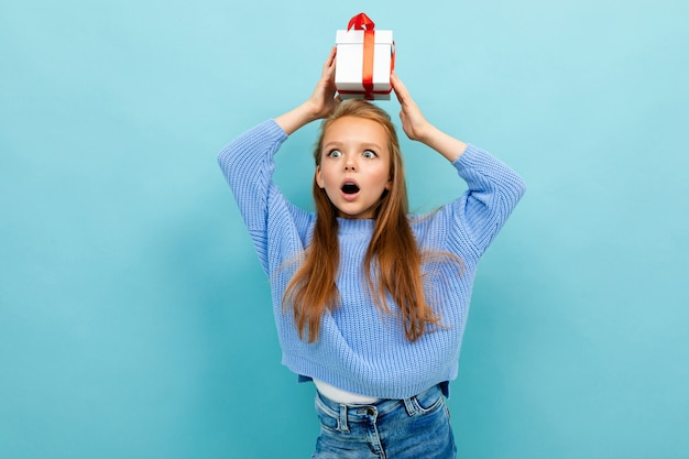 Atrakcyjna dziewczyna stoi przy ścianie z prezentem na głowie z czerwoną wstążką