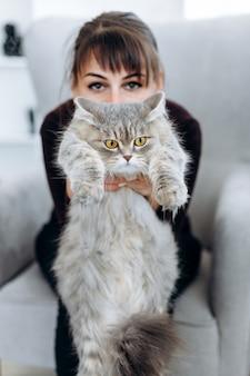 Atrakcyjna dziewczyna trzyma pięknego kota w jej rękach