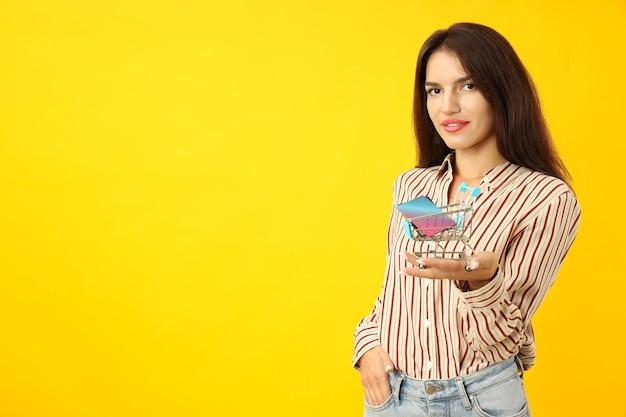 Atrakcyjna dziewczyna trzyma wózek sklepowy z kartami kredytowymi na żółtym tle.