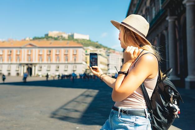 Atrakcyjna dziewczyna turystyczny w kapeluszu z plecakiem zwiedza nowe miasto w europie latem i robienie zdjęć przy użyciu swojego telefonu
