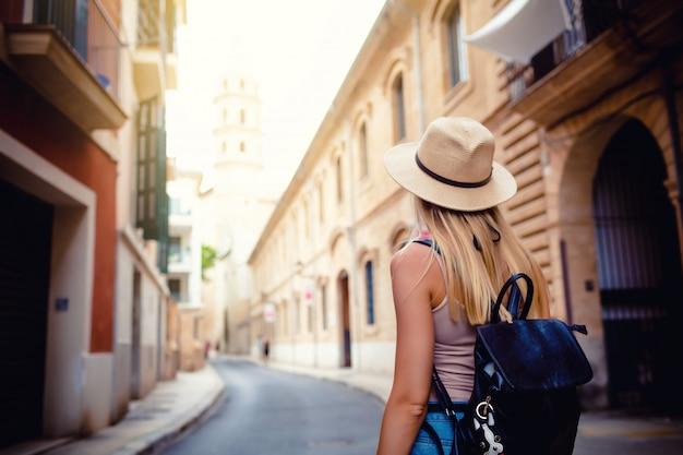Atrakcyjna dziewczyna turystycznych w kapeluszu z plecakiem zwiedzanie nowego miasta w europie latem