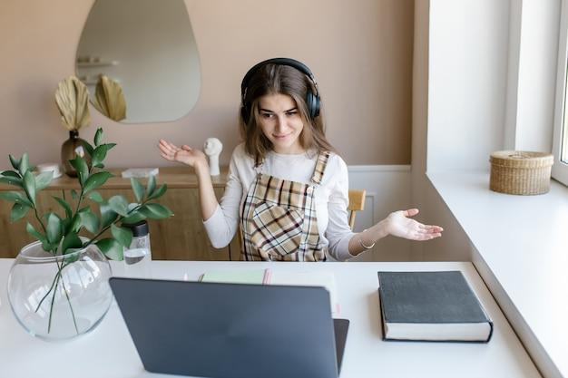 Atrakcyjna dziewczyna ubrana w słuchawki uczyć się z nauczycielem skype czatu internetowego przygotować się do egzaminu