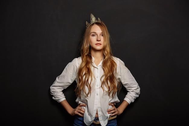 Atrakcyjna dziewczyna w białej koszuli z koroną na głowie