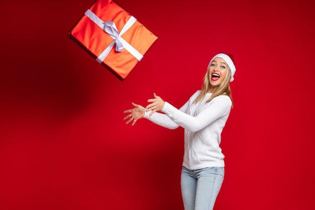 Atrakcyjna dziewczyna w czapce mikołaja z czerwonymi ustami ubrana w biały sweter z dzianiny rzuca prezent gwiazdkowy w czerwonym papierze z białą kokardką. na białym tle na czerwonej ścianie.