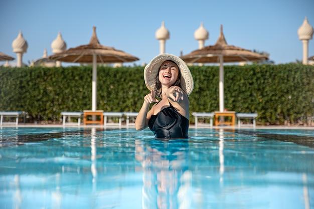 Atrakcyjna dziewczyna w czarnym stroju kąpielowym i kapeluszu kąpie się w basenie. pojęcie wypoczynku i rekreacji w ciepłym kraju.