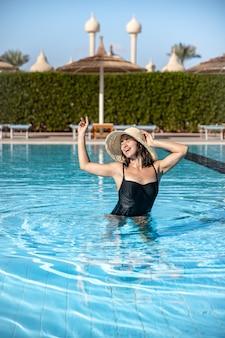 Atrakcyjna dziewczyna w czarnym stroju kąpielowym i kapeluszu kąpie się w basenie
