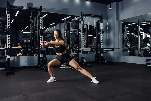 Atrakcyjna dziewczyna w czarnym stroju sportowym wykonuje funkcjonalne, spalające kalorie wypady boczne na sali gimnastycznej w mrocznej atmosferze