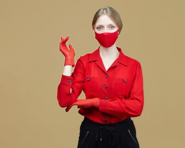 Atrakcyjna dziewczyna w czerwonych rękawiczkach i masce. koncepcja zapobiegania koronawirusowi covid 19. sesja zdjęciowa w pracowni na żółtym tle