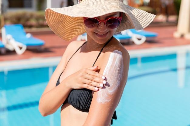 Atrakcyjna dziewczyna w kapeluszu, stosując krem do opalania na ramieniu przy basenie. współczynnik ochrony przeciwsłonecznej na wakacjach, koncepcja.