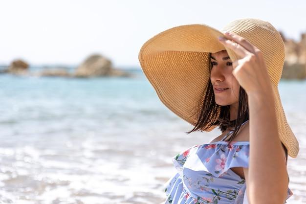 Atrakcyjna dziewczyna w kapeluszu ukrywa twarz przed słońcem, siedząc nad brzegiem morza.