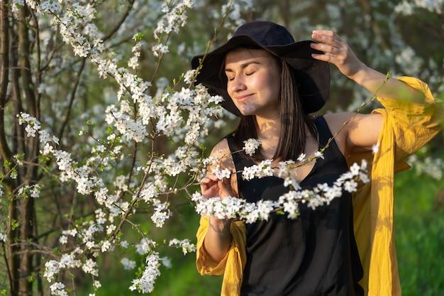 Atrakcyjna dziewczyna w kapeluszu wśród kwitnących drzew cieszy się zapachem wiosennych kwiatów