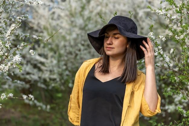 Atrakcyjna dziewczyna w kapeluszu wśród kwitnących drzew na wiosnę, w stylu casual